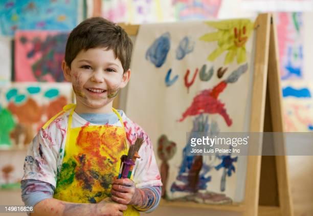 messy caucasian boy in art class - staffelei stock-fotos und bilder