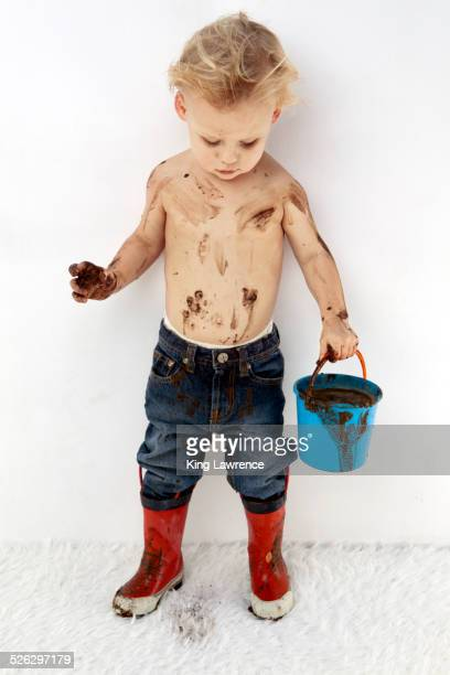 Messy Caucasian boy playing with mud on white carpet