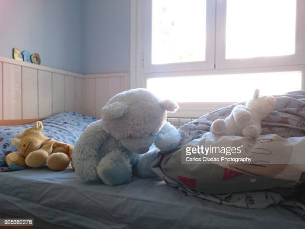 Messy child's bedroom with cuddly toys on unmade bed