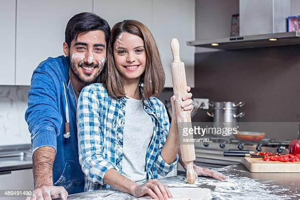 Desordenado pareja gente después de la preparación de la masa de pizza