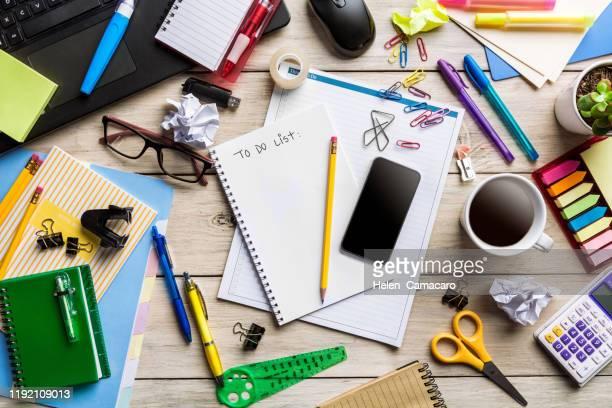 messy desktop with office supplies on rustic wooden table - disordinato foto e immagini stock