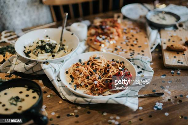 messy dining table with leftover food covered with confetti after party celebration - table after party stock pictures, royalty-free photos & images