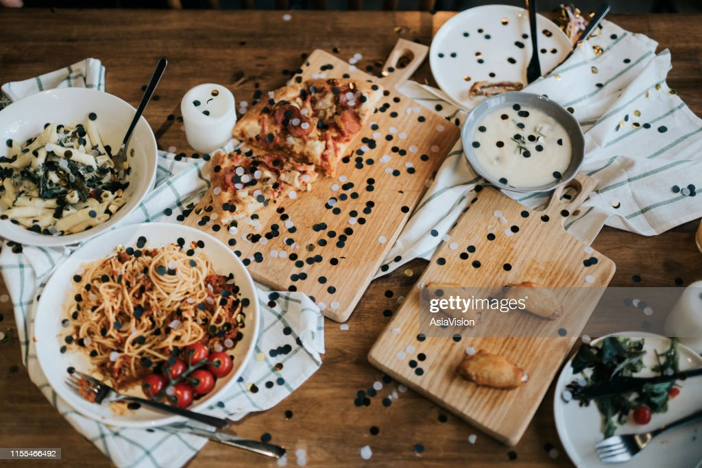 Messy dining table with leftover food covered with confetti after party celebration : Stock Photo
