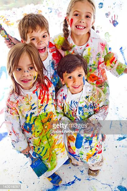 Messy Hispanic children covered in paint