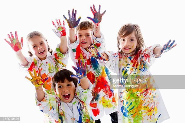 Messy Hispanic children finger painting