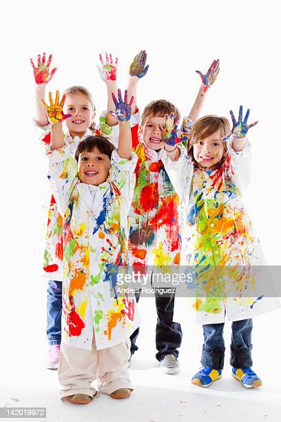 Messy Hispanic children finger painting