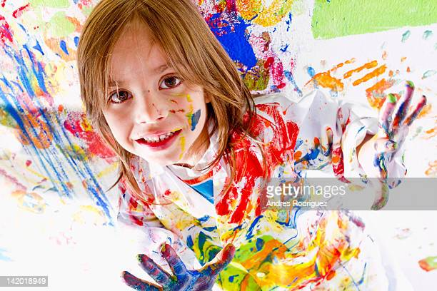Messy Hispanic girl finger painting