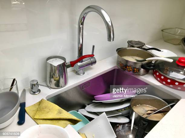 Messy sink full of dishes
