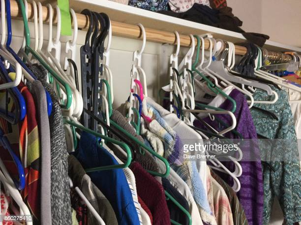 messy walk-in closet with plastic hangers - walk in closet stock photos and pictures
