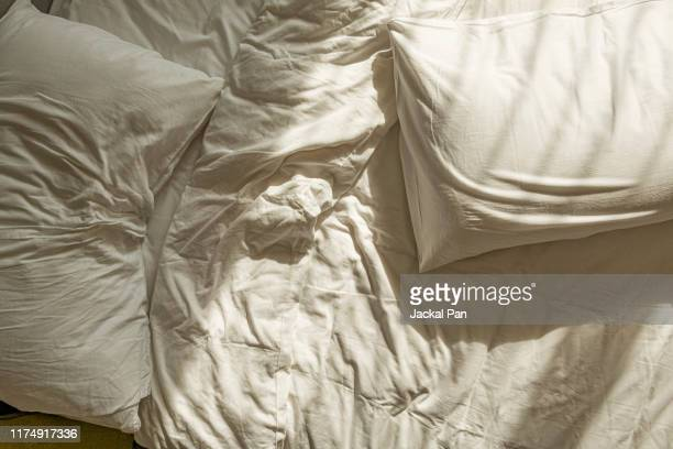 messy white sheet on bed - 枕 ストックフォトと画像