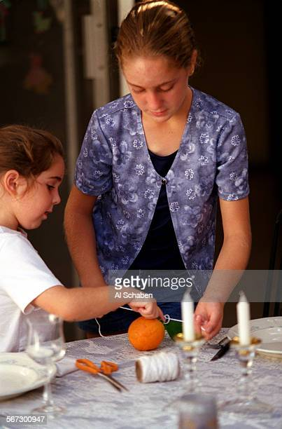 MEsukkottwo1003AS––FOUNTAIN VALLEY––Eliana left and Shayna Rosen tie string to an orange as they construct a sukkah a makeshift hut made with wood...