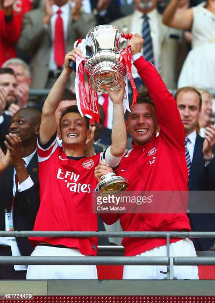 Mesut Oezil and Lukas Podolsk of Arsenal lift the trophy in celebration after the FA Cup with Budweiser Final match between Arsenal and Hull City at...