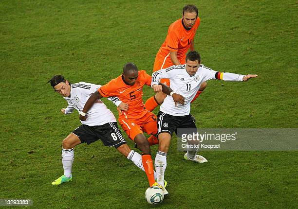 Mesut Oezil and Miroslav Klose of Germany challenge Edson Braafheid of Netherlands during the International friendly match between Germany and...