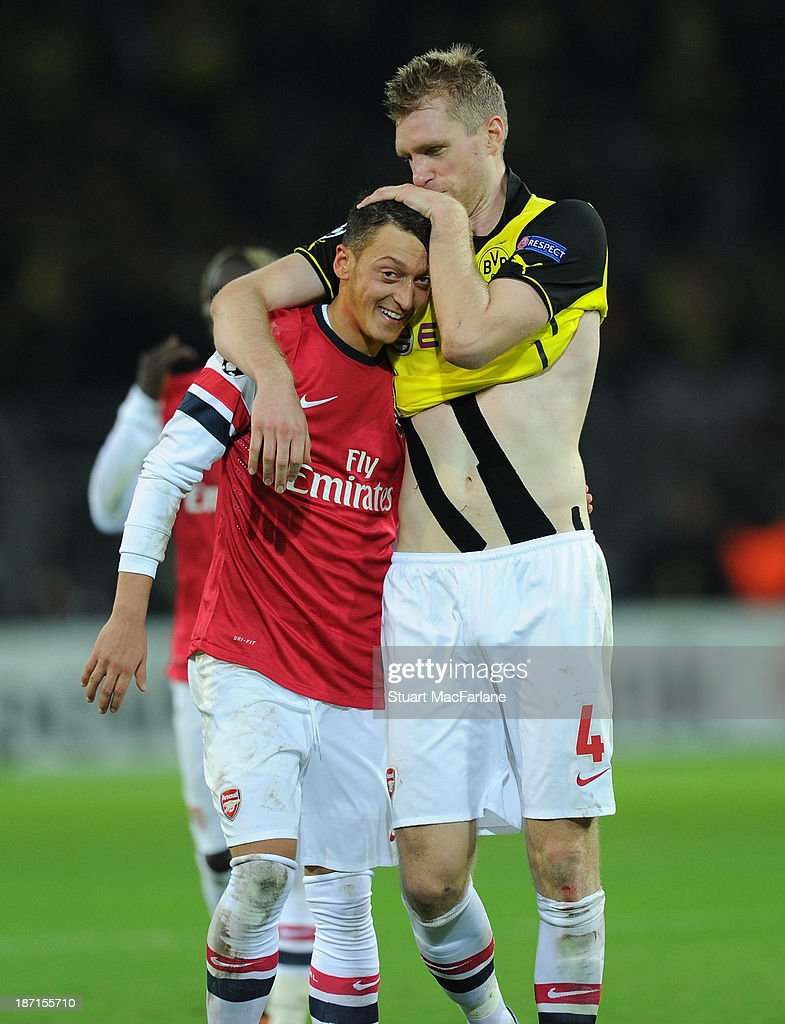Mesut Oezil and Per Mertesacker of Arsenal celebrate at the end of the UEFA Champions League Group F match between Borussia Dortmund and Arsenal at Signal Iduna Park on November 6, 2013 in Dortmund, Germany.