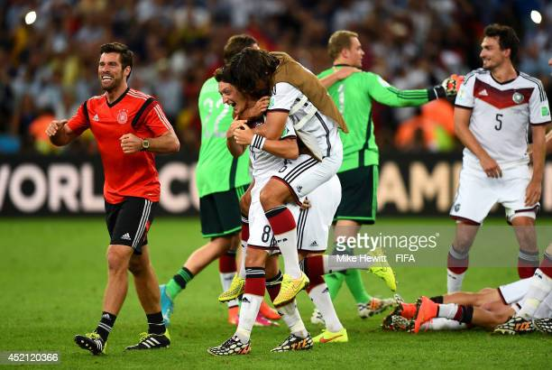 Mesut Oezil and Sami Khedira of Germany celebrate after the 10 win in the 2014 FIFA World Cup Brazil Final match between Germany and Argentina at...