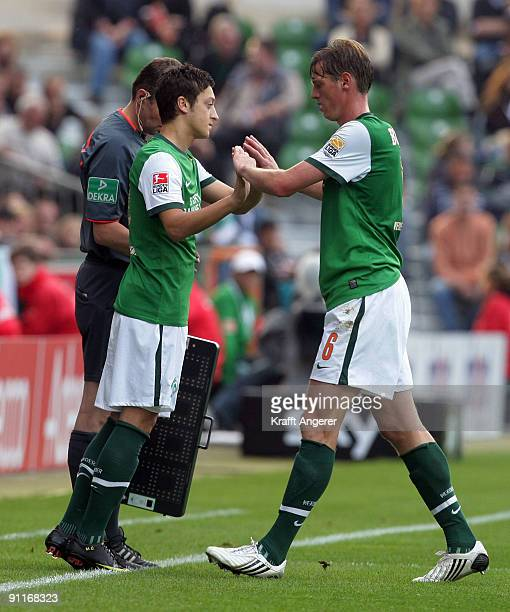 Mesut Oezil and Tim Borowski of Bremen shake hands during the Bundesliga match between SV Werder Bremen and FSV Mainz 05 at Weser Stadium on...
