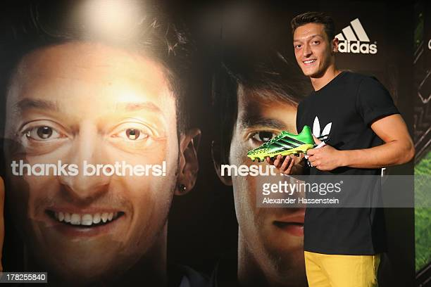 Mesut Oezil holds his new Predator boots during the adidas presentation of the new campaign Welcoming Mesut to the family in the adidas store at the...