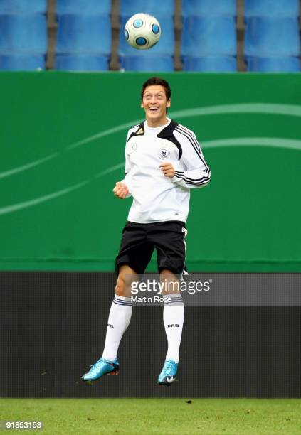 Mesut Oezil jumps for a header the ball during the German National Team training session at the Hamburg Arena on October 13 2009 in Hamburg Germany