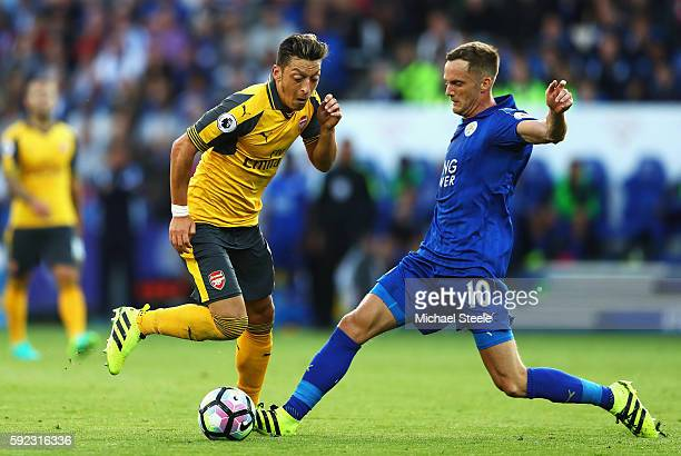 Mesut Oezil of Arsenal and Andy King of Leicester City battle for possession during the Premier League match between Leicester City and Arsenal at...