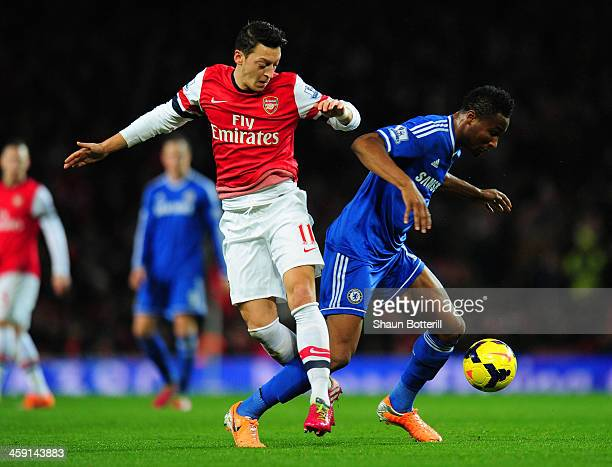 Mesut Oezil of Arsenal and John Obi Mikel of Chelsea compete for the ball during the Barclays Premier League match between Arsenal and Chelsea at...