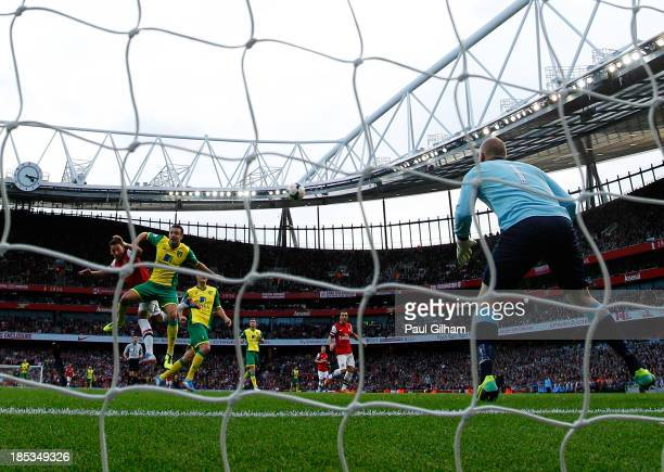 Mesut Oezil of Arsenal beats Russell Martin of Norwich City as he scores their second goal with a header past goalkeeper John Ruddy during the...