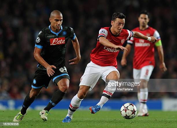 Mesut Oezil of Arsenal breaks past Gokhan Inler of Napoli during the UEFA Champions League Group F match between Arsenal FC and SSC Napoli at...