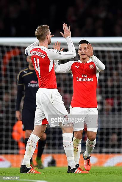 Mesut Oezil of Arsenal celebrates scoring his side's first goal with Per Mertesacker of Arsenal during the UEFA Champions League match between...
