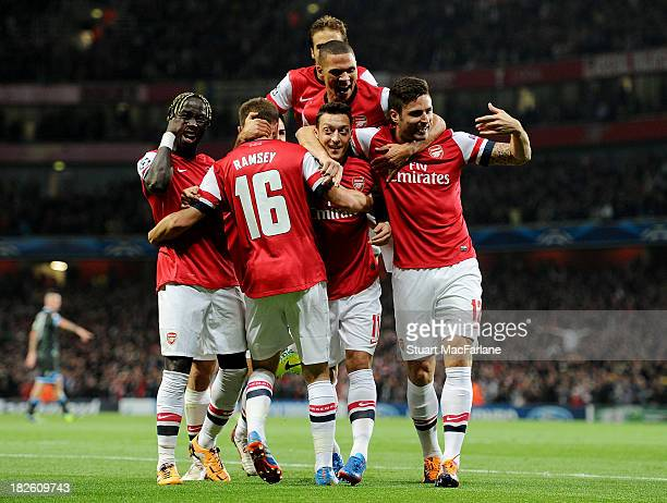 Mesut Oezil of Arsenal celebrates scoring his team's 1st goal with Bacary Sagna Aaron Ramsey Kieran Gibbs Mathieu Flamini and Olivier Giroud during...