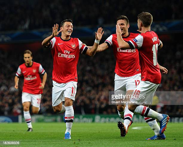 Mesut Oezil of Arsenal celebrates scoring his team's first goal with Olivier Giroud and Aaron Ramsey during the UEFA Champions League Group F match...