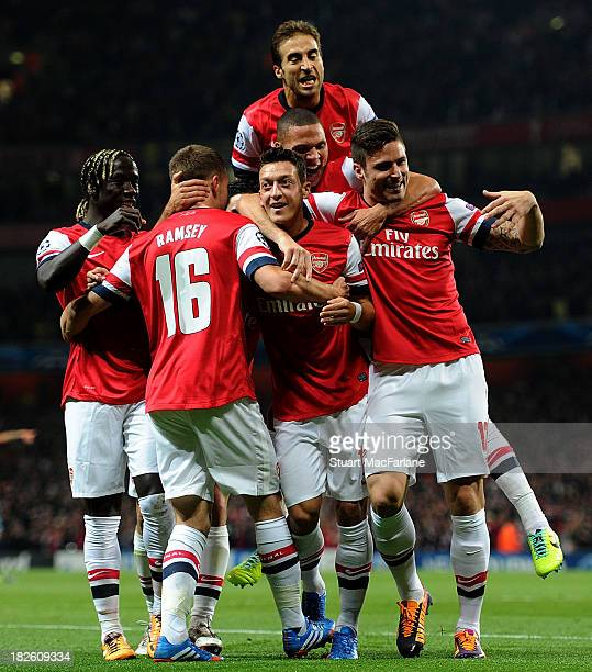Mesut Oezil of Arsenal celebrates scoring his team's first goal with Bacary Sagna Aaron Ramsey Kieran Gibbs Mathieu Flamini and Olivier Giroud during...