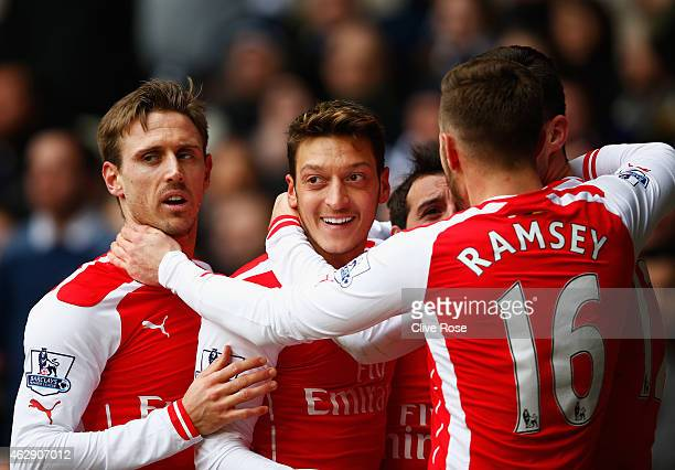 Mesut Oezil of Arsenal celebrates scoring the opening goal with team mates during the Barclays Premier League match between Tottenham Hotspur and...