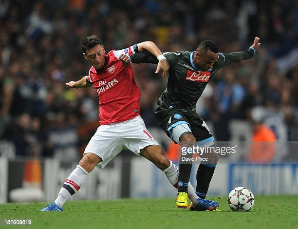 Mesut Oezil of Arsenal challenges Camilo Zuniga of Napoli during the UEFA Champions League Group F match between Arsenal FC and SSC Napoli at...