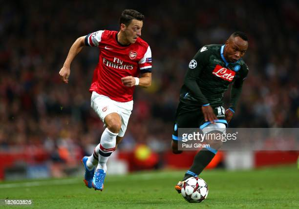 Mesut Oezil of Arsenal goes past Camilo Zuniga of Napoli during UEFA Champions League Group F match between Arsenal FC and SSC Napoli at Emirates...