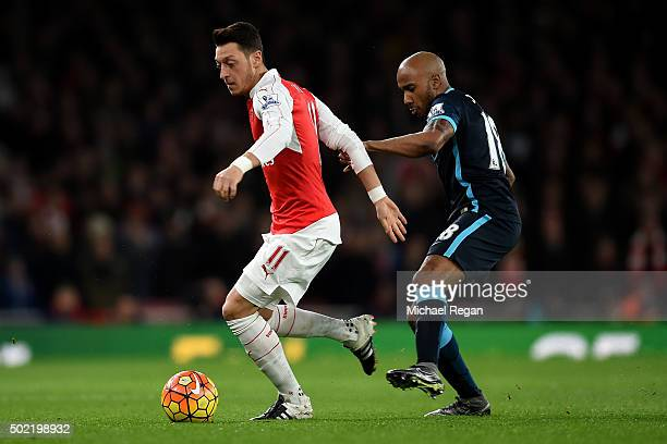 Mesut Oezil of Arsenal holds off Fabian Delph of Manchester City during the Barclays Premier League match between Arsenal and Manchester City at...