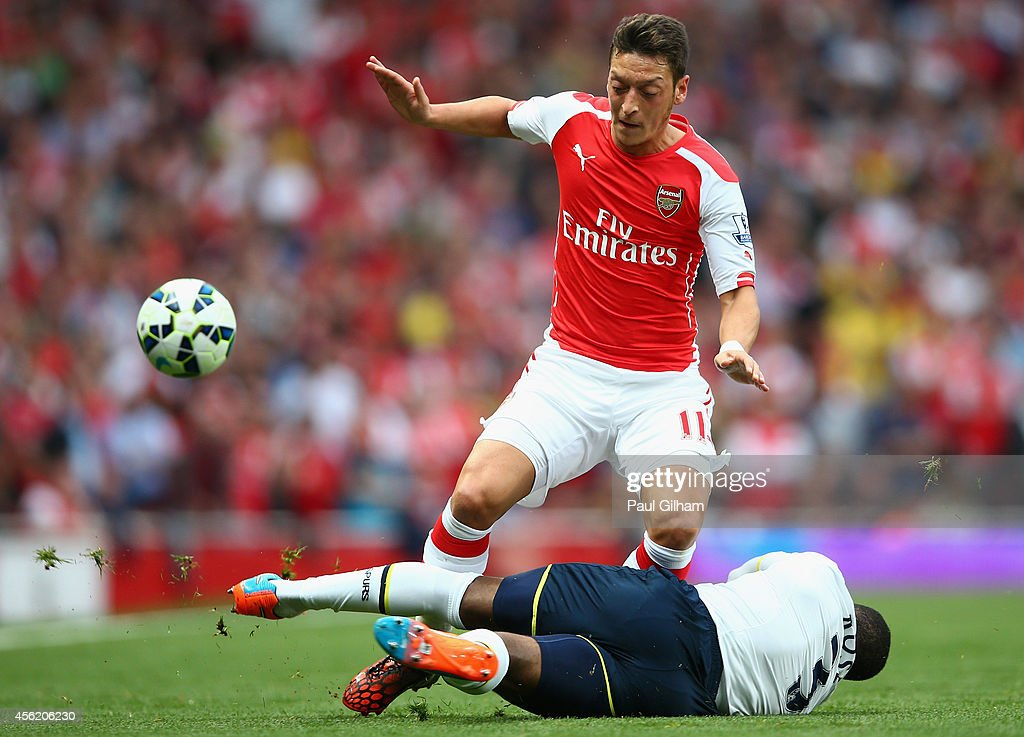 Mesut Oezil of Arsenal in action against Danny Rose of Spurs during the Barclays Premier League match between Arsenal and Tottenham Hotspur at Emirates Stadium on September 27, 2014 in London, England.