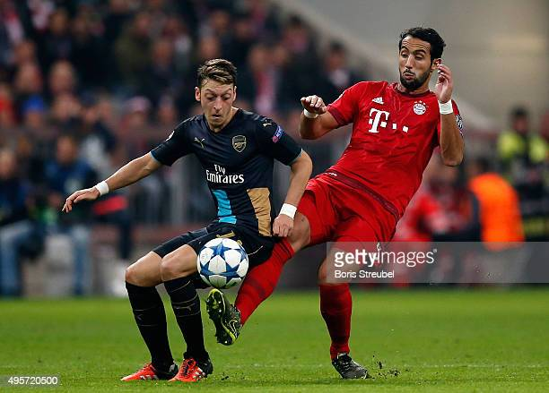 Mesut Oezil of Arsenal is challenged by Medhi Benatia of Bayern Muenchen during the UEFA Champions League Group F match between FC Bayern Muenchen...