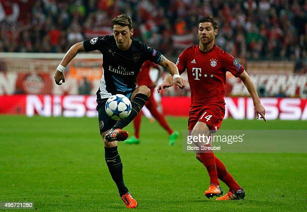 Mesut Oezil of Arsenal is challenged by Xabi Alonso of Bayern Muenchen during the UEFA Champions League Group F match between FC Bayern Muenchen and...