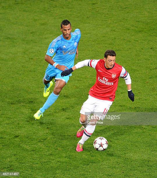 Mesut Oezil of Arsenal is closed down by Alaixys Romao of Marseille during the match between Arsenal and Marseille at Emirates Stadium on November 26...
