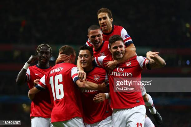 Mesut Oezil of Arsenal is congratulated by teammates after scoring the opening goal during UEFA Champions League Group F match between Arsenal FC and...