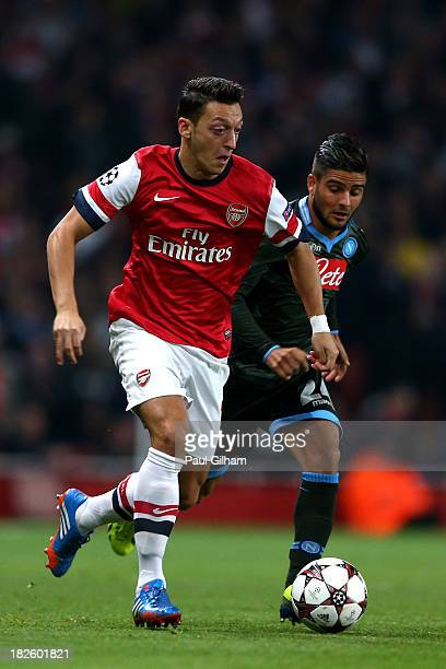 Mesut Oezil of Arsenal is pursued by Lorenzo Insigne of Napoli during UEFA Champions League Group F match between Arsenal FC and SSC Napoli at...