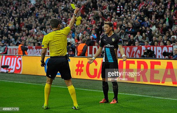 Mesut Oezil of Arsenal is shown a yellow card by Referee Gianluca Rocchi during the UEFA Champions League Group F match between FC Bayern Muenchen...