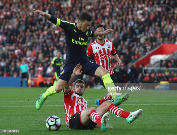 Mesut Oezil of Arsenal is tackled by Jack Stephens of Southampton during the Premier League match between Southampton and Arsenal at St Mary's...