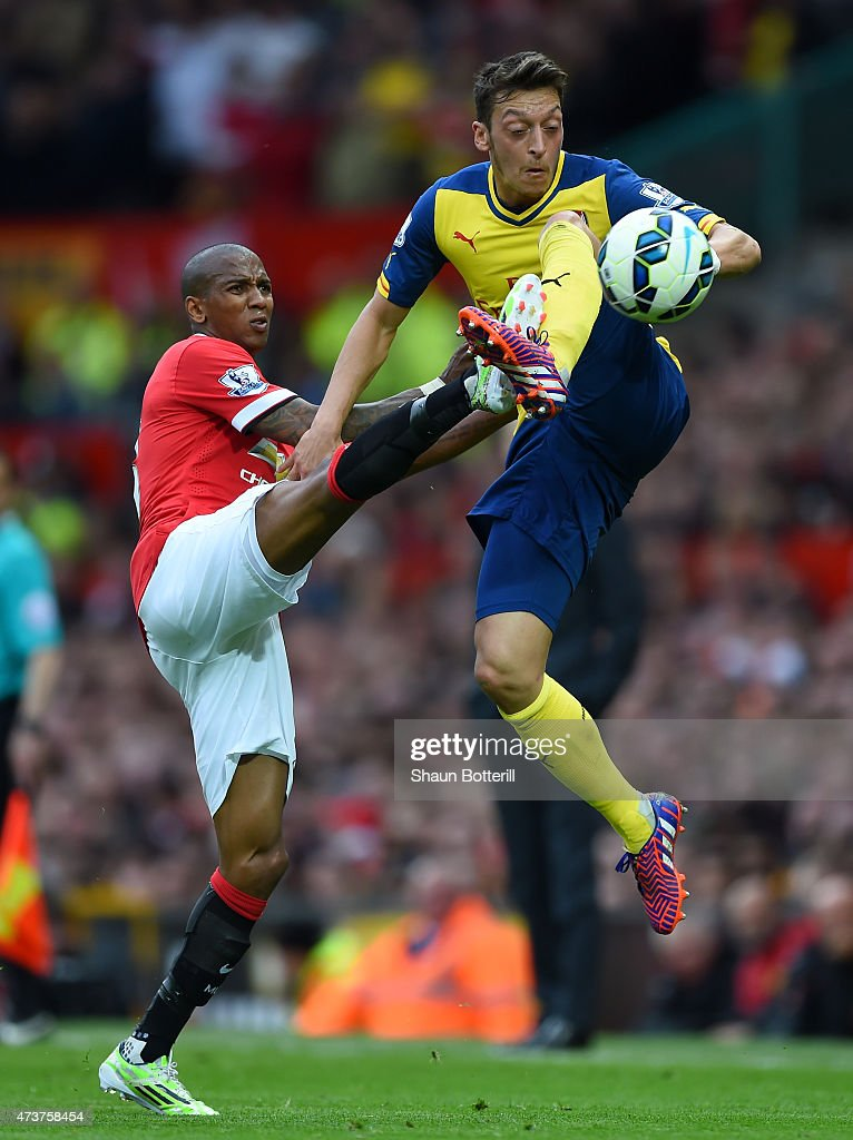 Mesut Oezil of Arsenal jumps for the ball with Ashley Young of Manchester United during the Barclays Premier League match between Manchester United and Arsenal at Old Trafford on May 17, 2015 in Manchester, England.