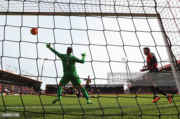 Mesut Oezil of Arsenal shoots past goalkeeper Artur Boruc of Bournemouth to score their first goal during the Barclays Premier League match between...