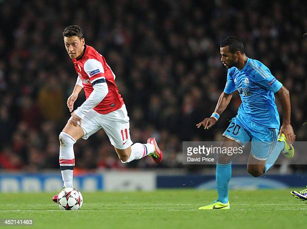 Mesut Oezil of Arsenal takes on Alaixys Romao of Marseille during the match between Arsenal and Marseille at Emirates Stadium on November 26 2013 in...