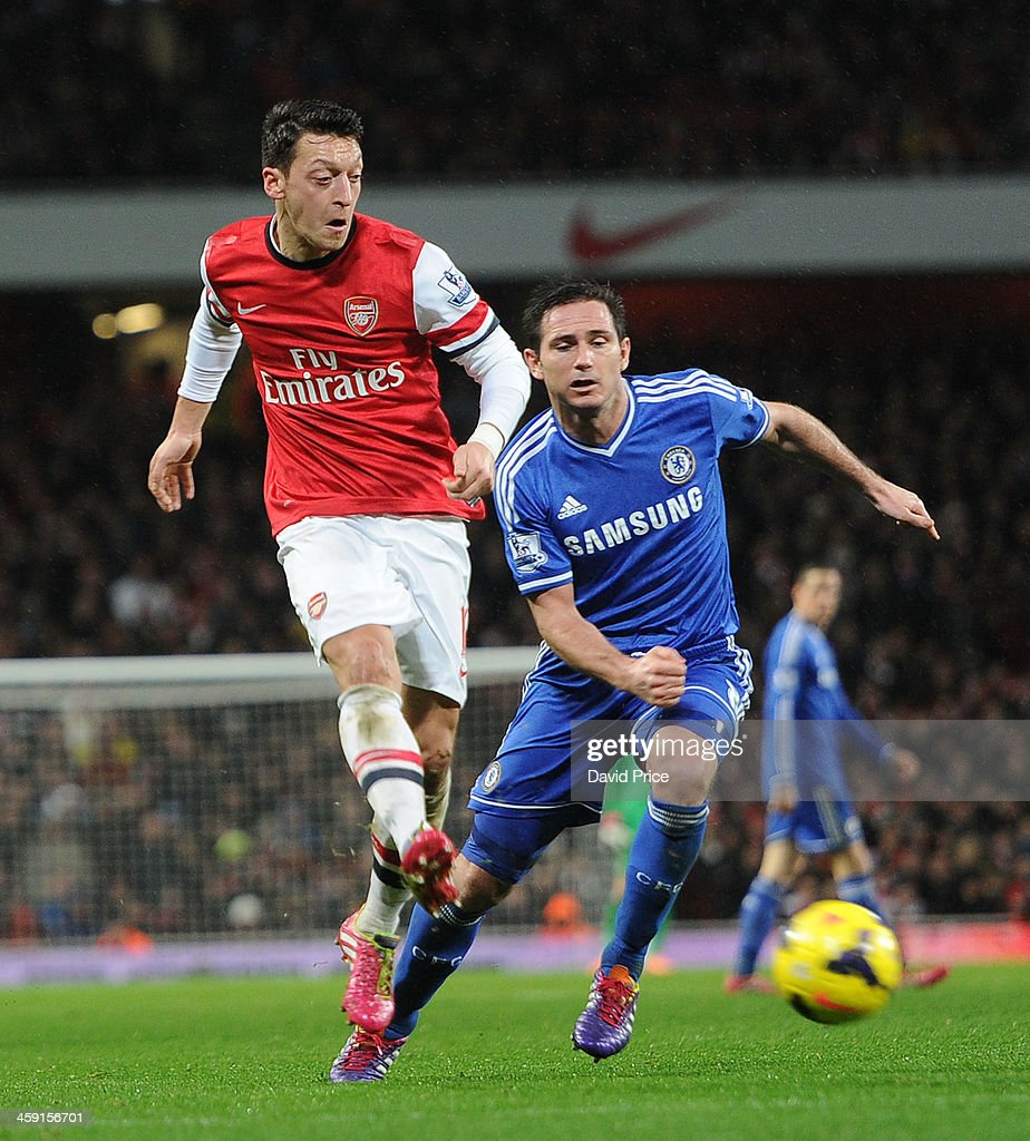 Mesut Oezil of Arsenal takes on Frank Lampard of Chelsea during the match between Arsenal and Chelsea in the Barclays Premier League at Emirates Stadium on December 23, 2013 in London, England.