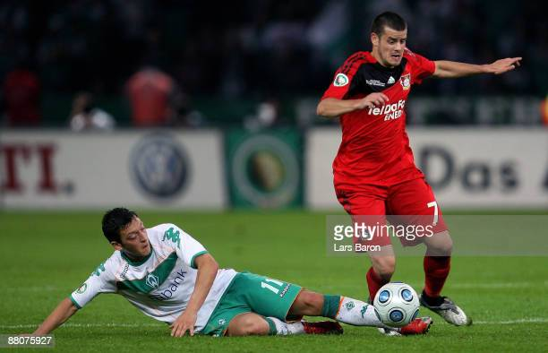 Mesut Oezil of Bremen challenges Tranquillo Barnetta of Leverkusen during the DFB Cup Final match between Bayer 04 Leverkusen and SV Werder Bremen at...