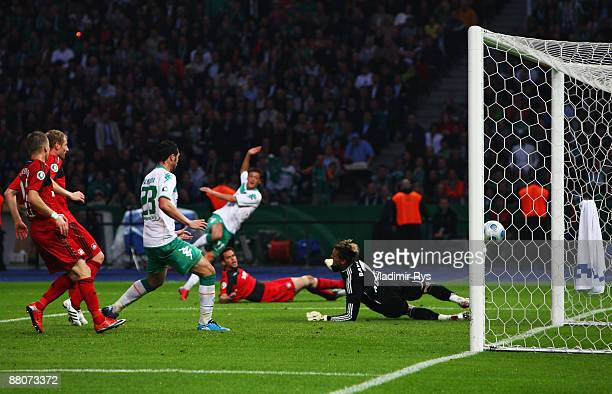 Mesut Oezil of Bremen scores his team's first goal against goalkeeper Rene Adler of Leverkusen during the DFB Cup Final match between Bayer 04...