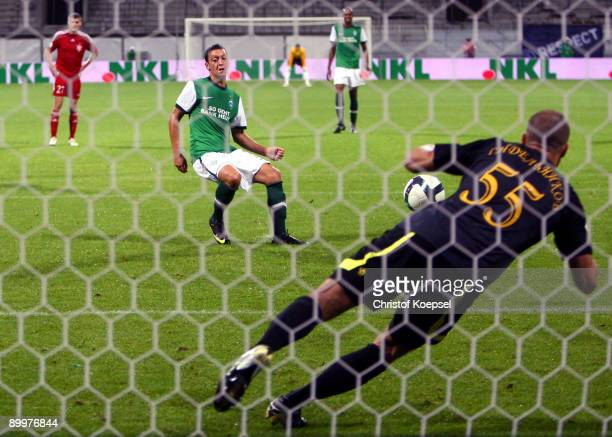 Mesut Oezil of Bremen scores his team`s sixth goal by penalty against goalkeeper Andrey Sidelnikov of Aktobe during the UEFA Europa League first leg...