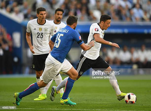 Mesut Oezil of Germany and Andrea Barzagli of Italy compete for the ball during the UEFA EURO 2016 quarter final match between Germany and Italy at...